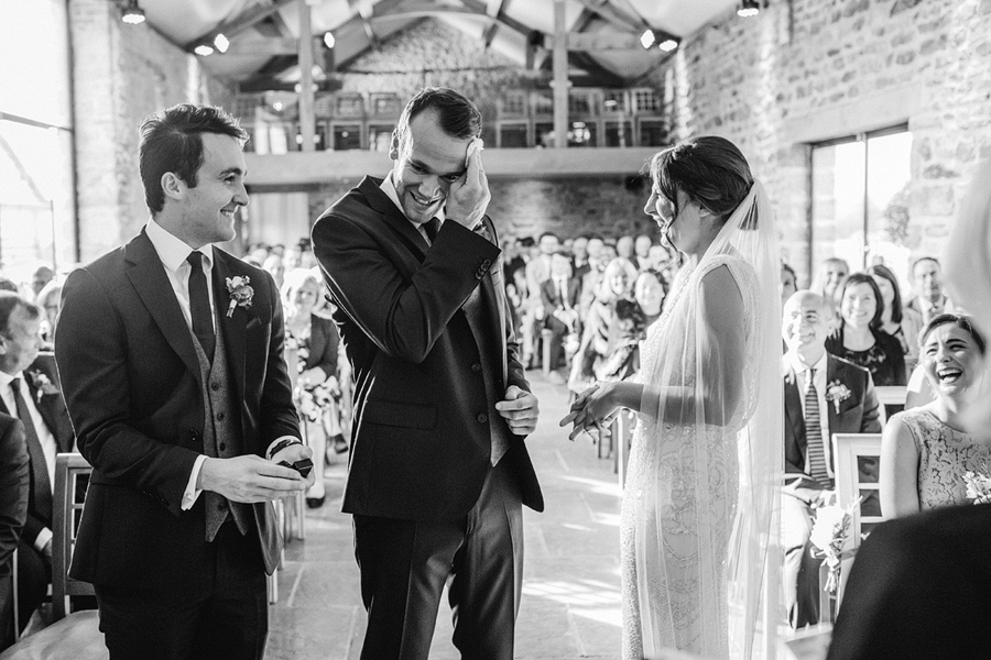 bride and groom nervously exchange their vows - photographed by Fawsley Hall wedding photographer