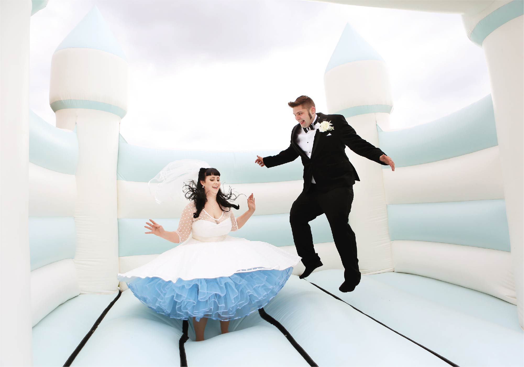 groom and bride jump on bouncy castle captured by Northampton wedding photgrapher Elliot W Patching
