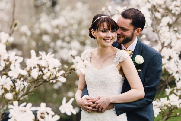 bride and groom with a backdrop of beautiful white flowers by Northamptonshire wedding photographer