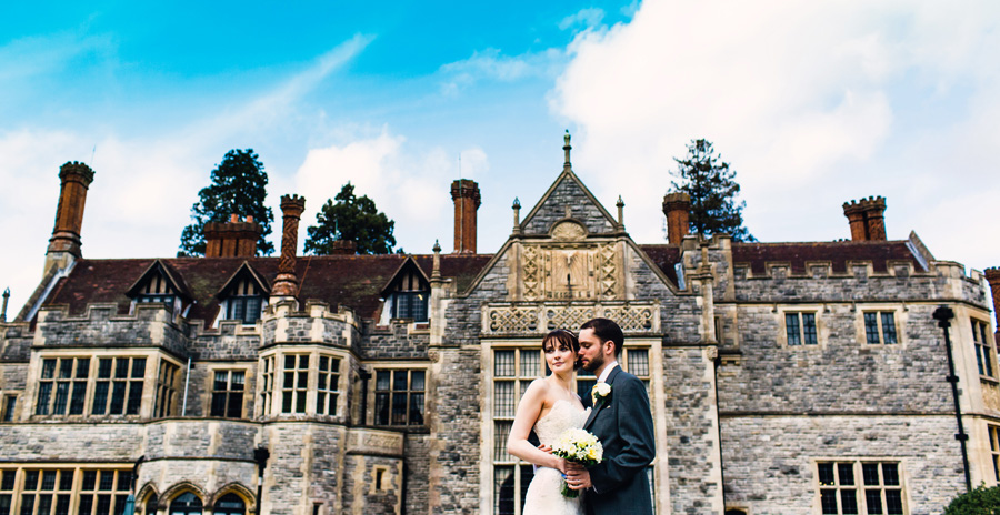 a bride and groom pose for photographs outside rhinefield house