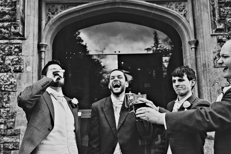 the groom and his groomsmen enjoy a drink and a laugh