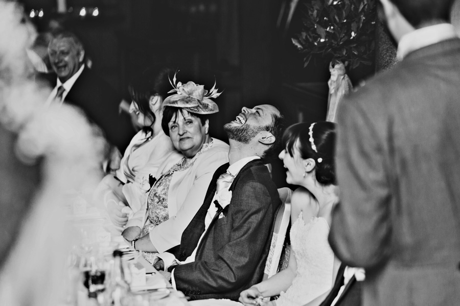 a black and white image of a groom during the wedding speeches