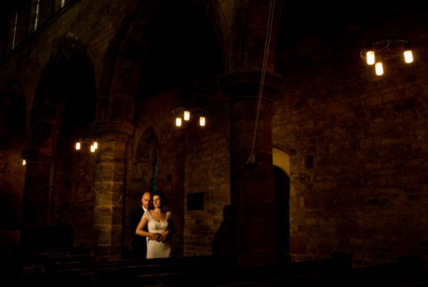 groom and bride in low light church, captured by Cotswold wedding photographer