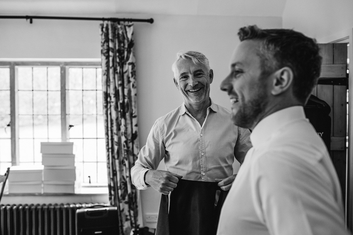 The father of the groom shares a joke with his son