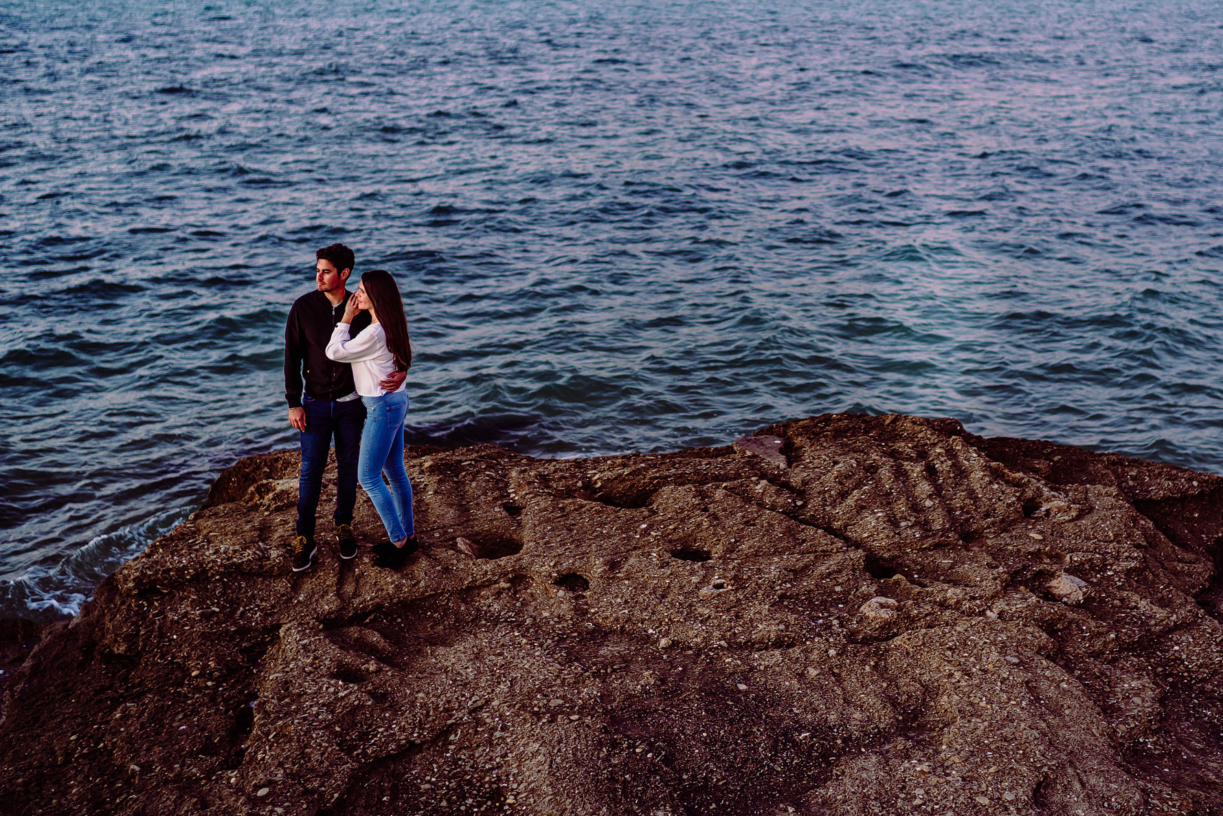 a couple embrace by the sea