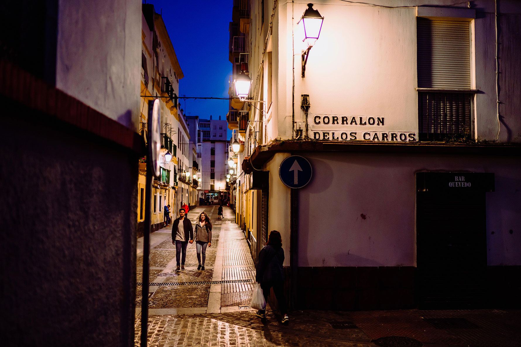 a couple walk through the streets of Cadiz at sunset