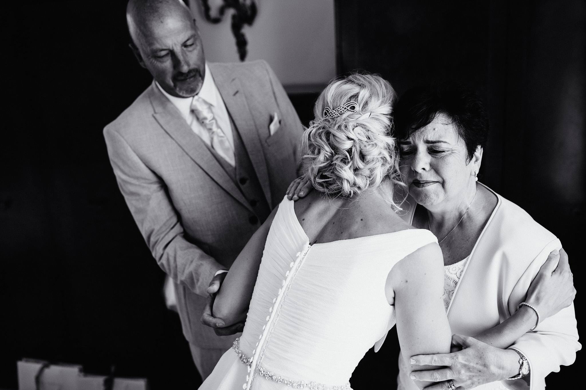 an emotional image of a bride with her parents