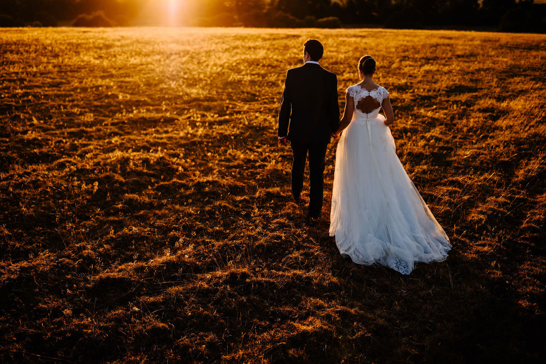 a bride and groom walking into the sunset