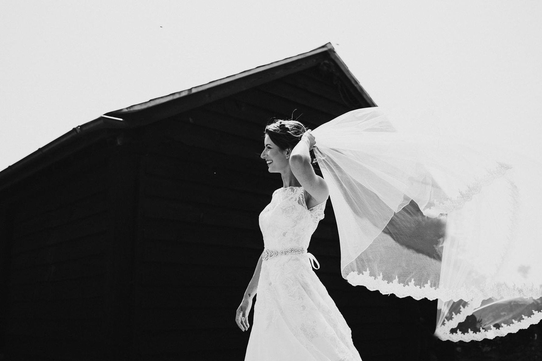 a black and white image of a bride and her veil