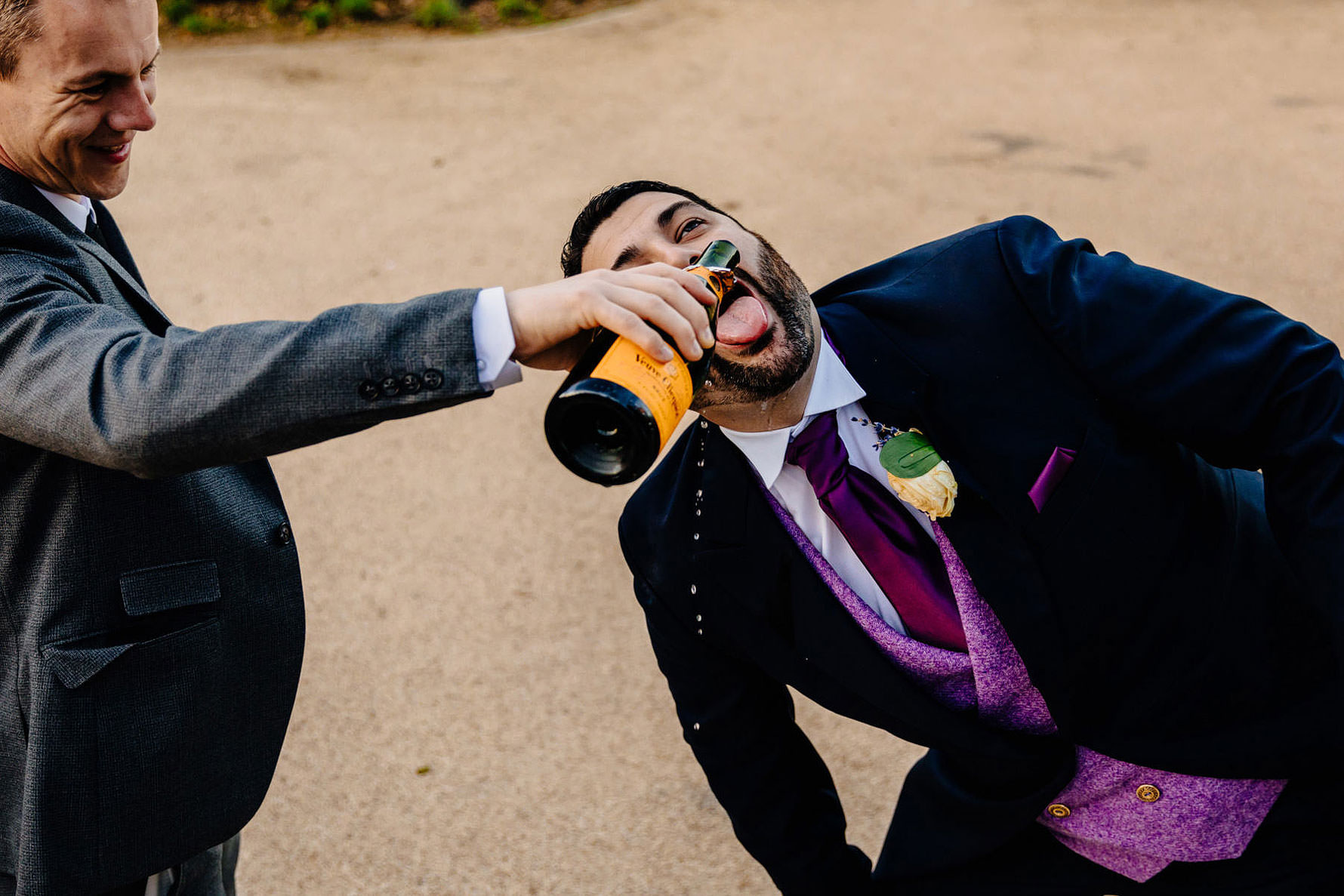 champagne being poured into the grooms mouth