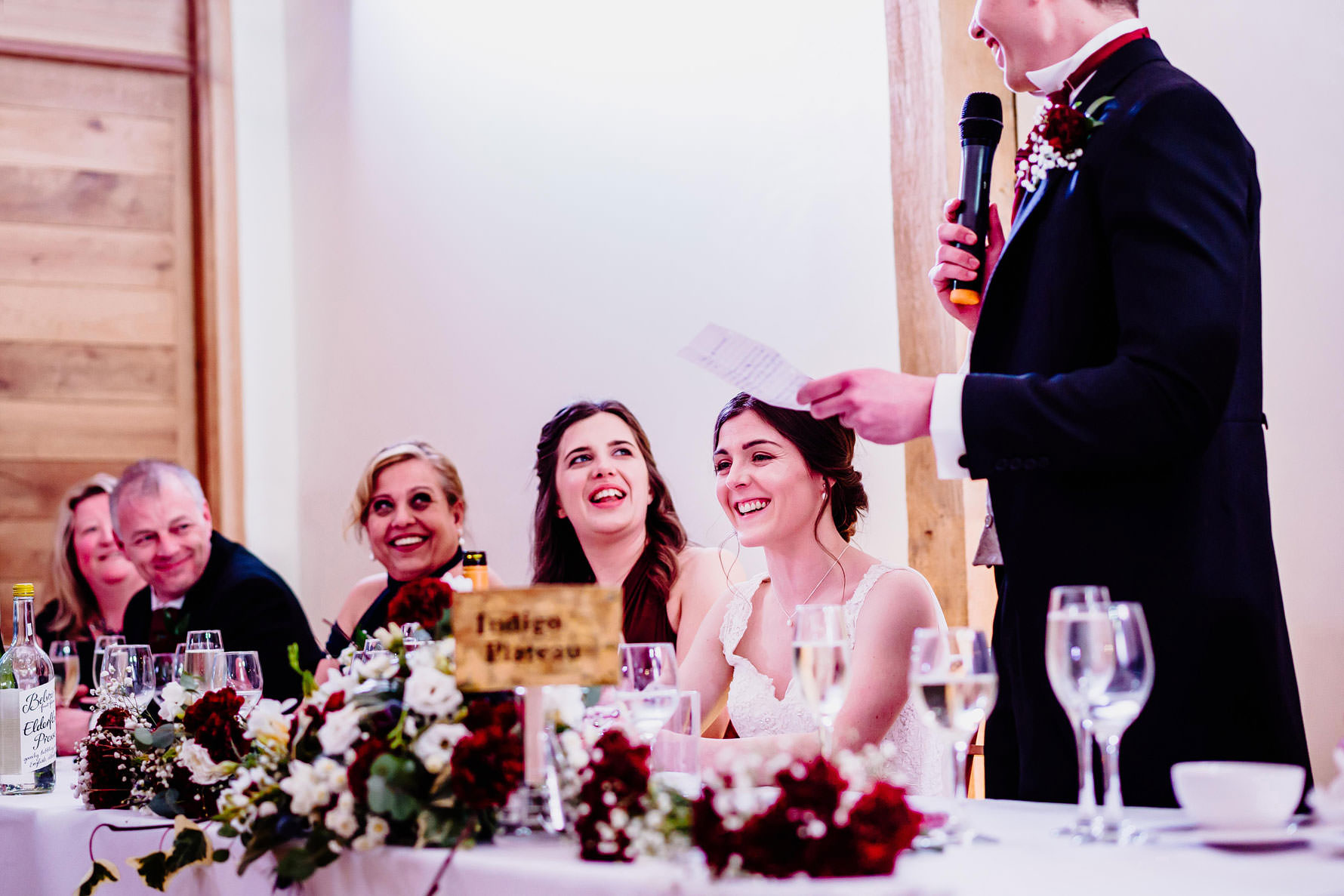 a bride laughs durning wedding speeches