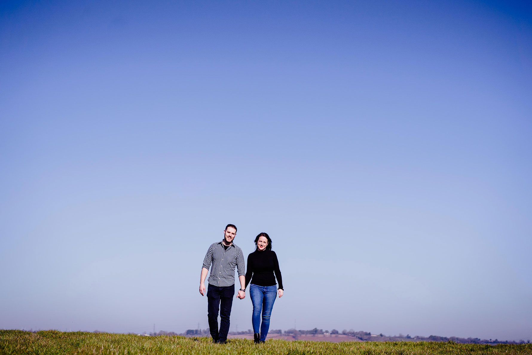 a images from an engagement shoot by Elliot w patching with a happy couple and a beautiful blue sky