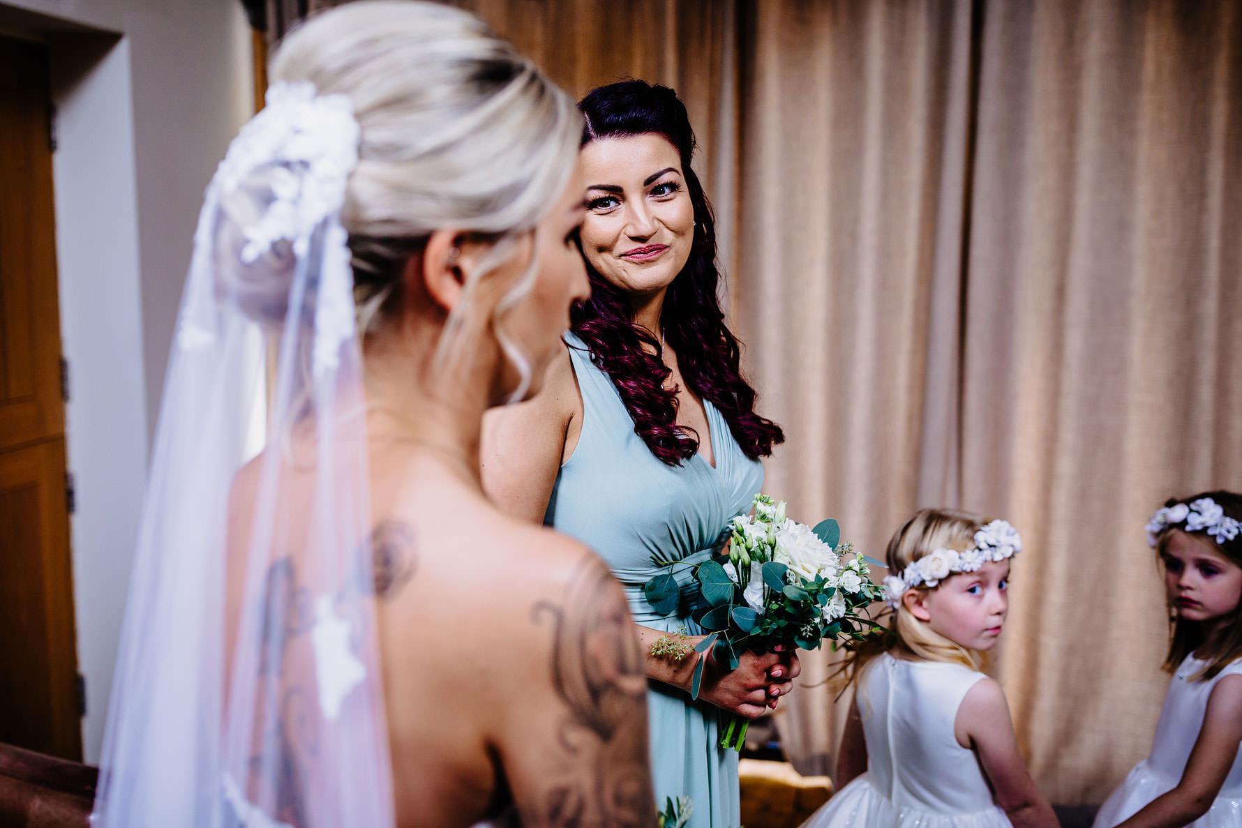 a bridesmaid looking adoringly at a bride