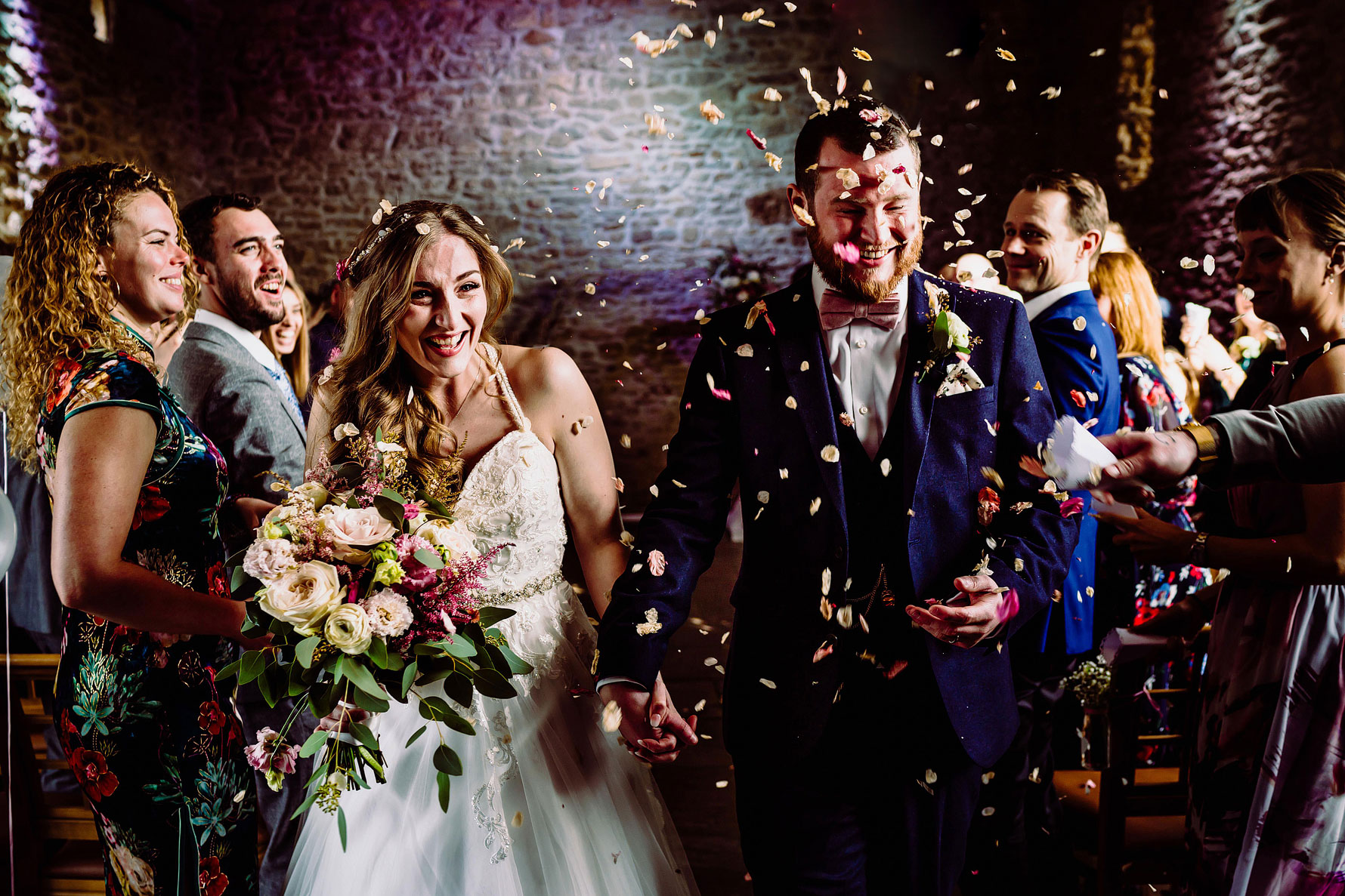 a bring and groom get covered in confetti