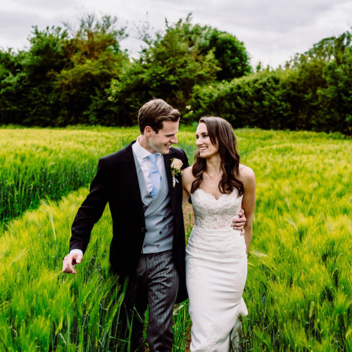 A bride and groom walk through a field at caswell house