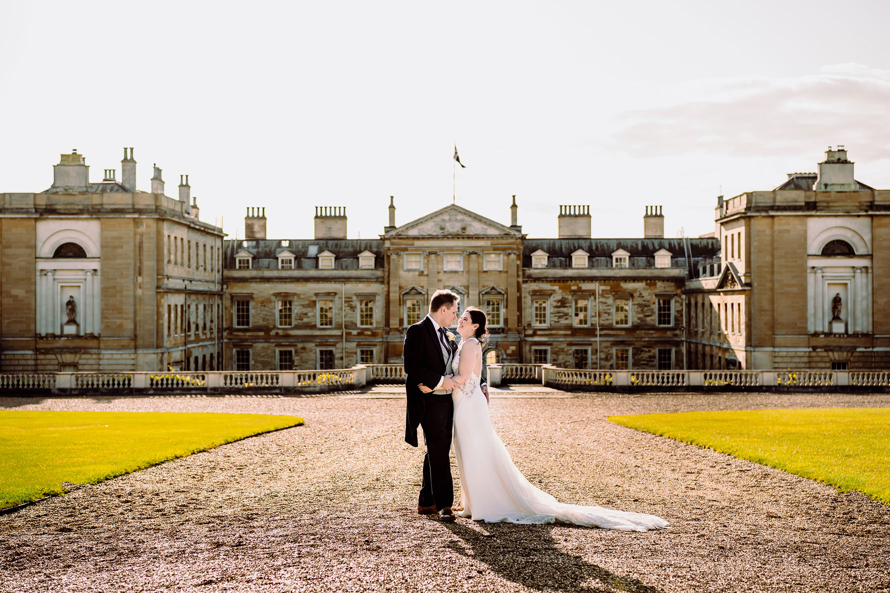 a bride and groom embrace in front of woburn abbey