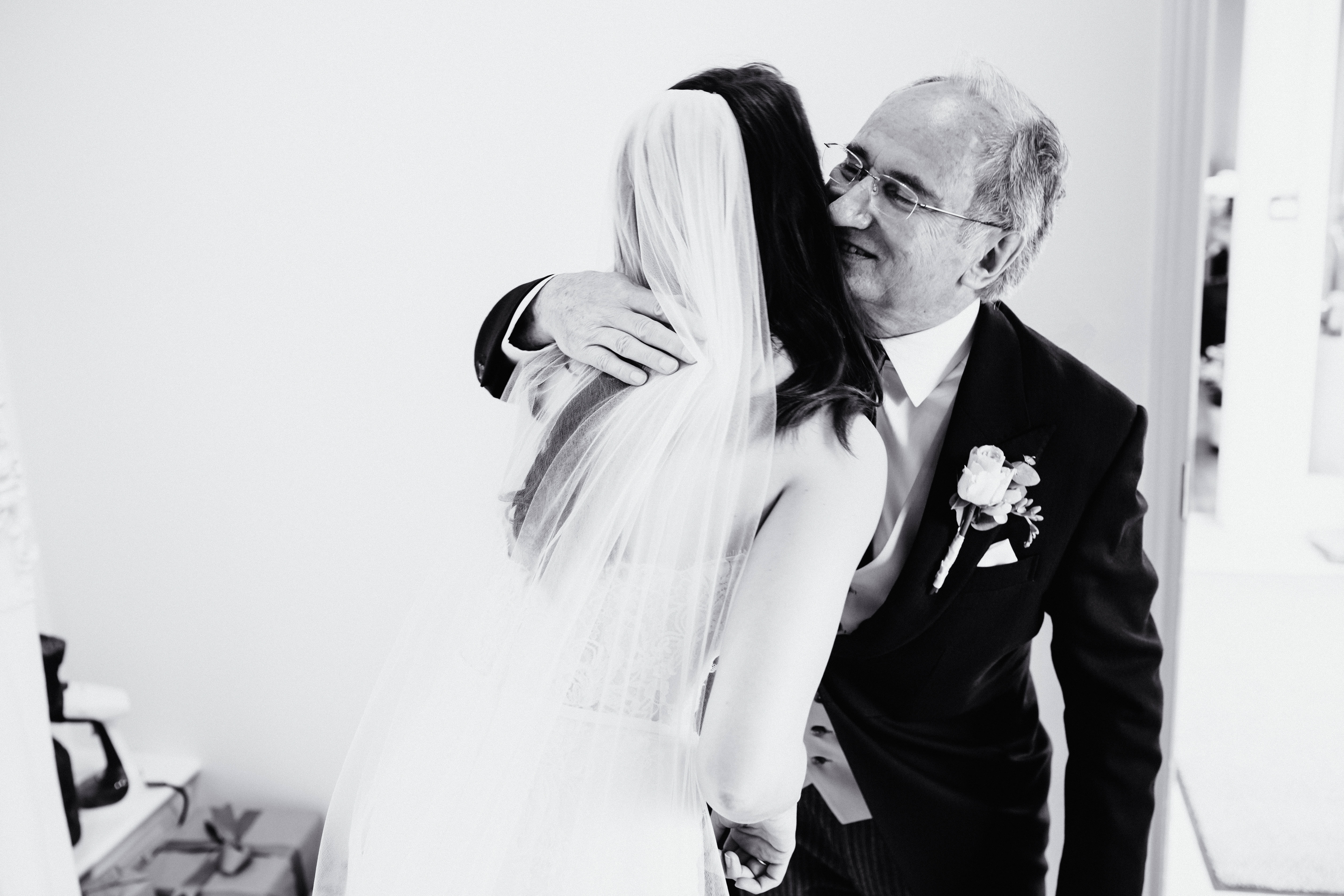 a father of the bride embraces his daughter
