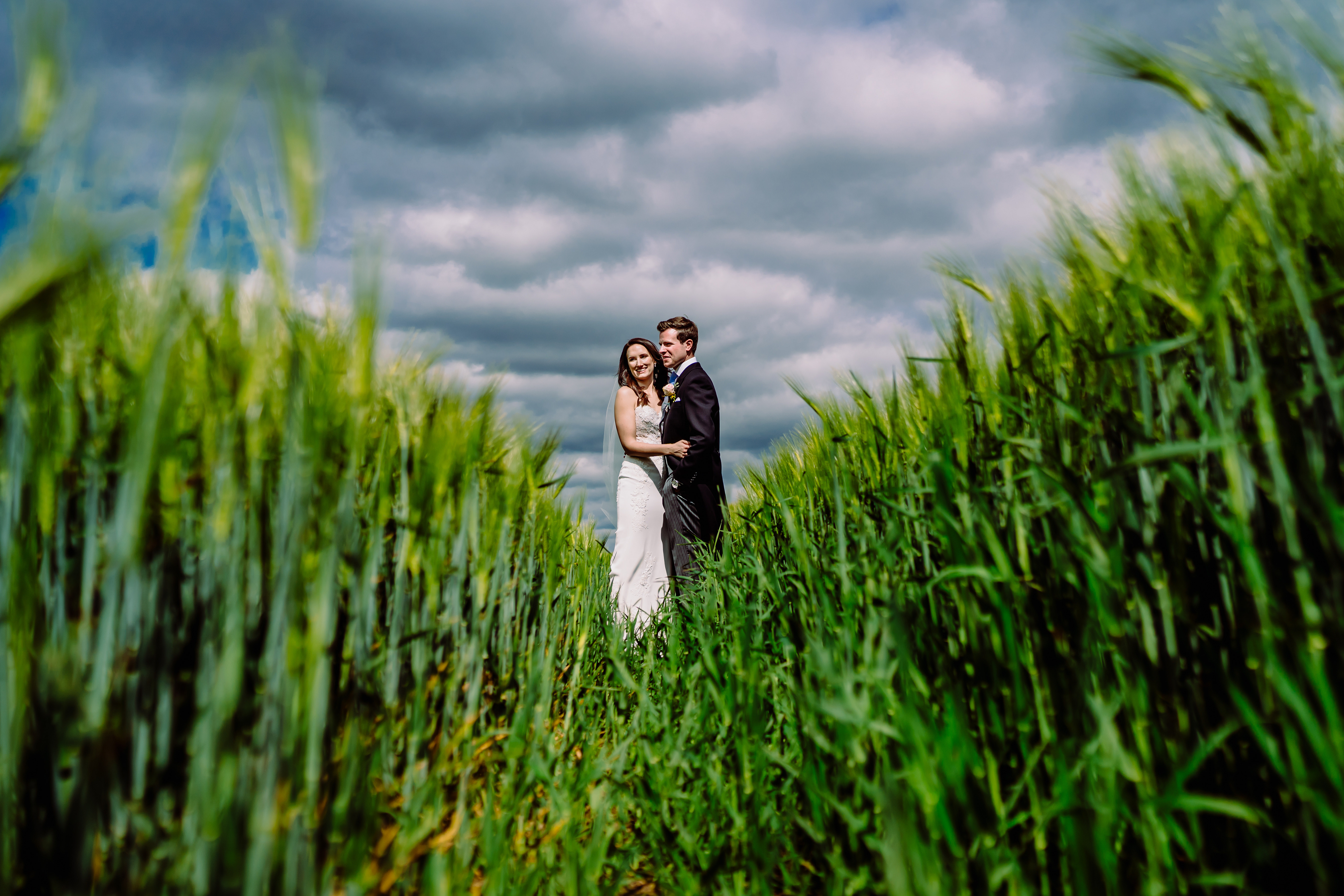 a bride and groom in a field