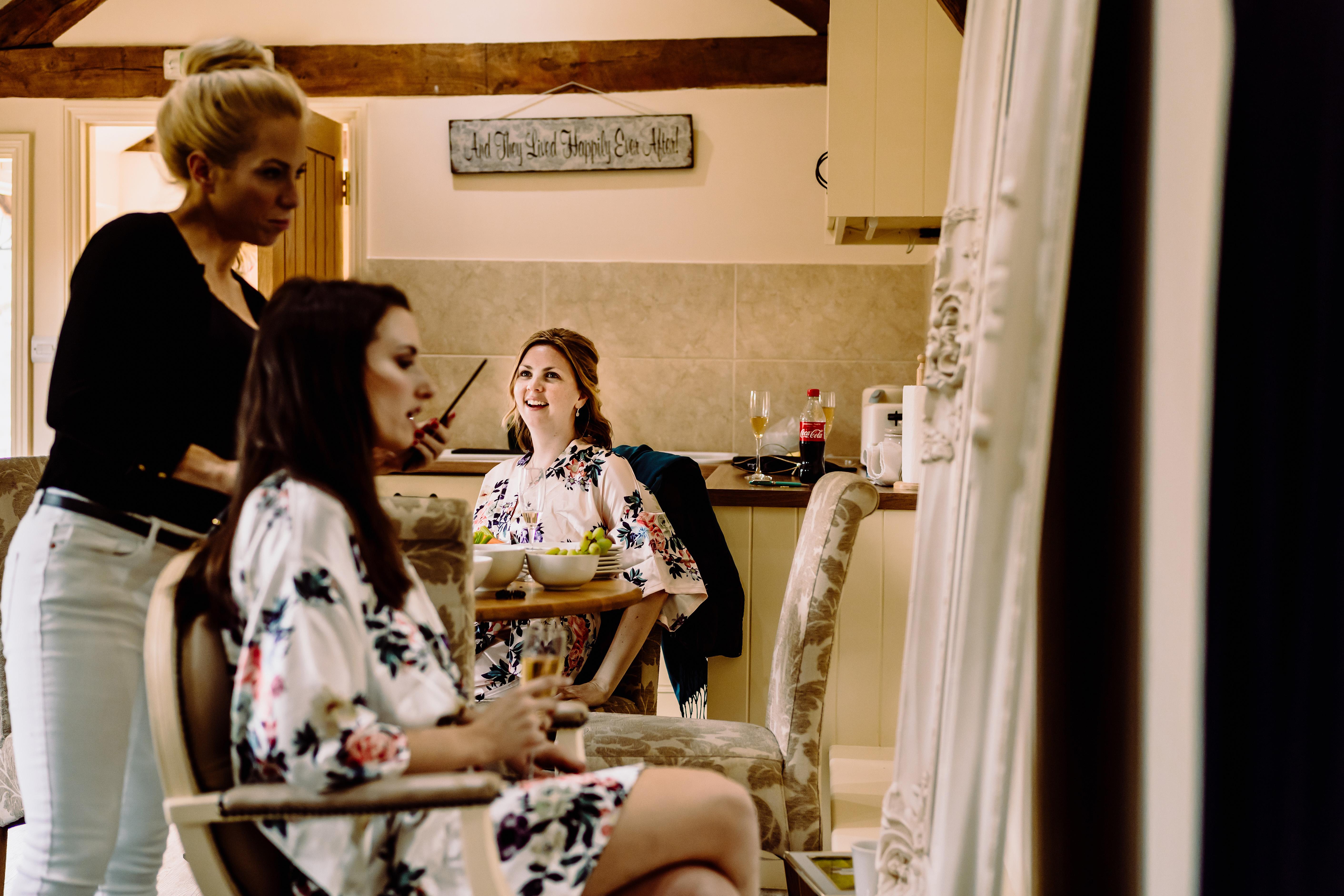 a bridesmaid watches a bride prepare