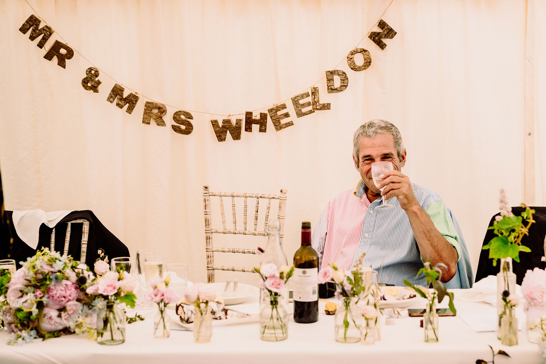father of the bride drinking wine