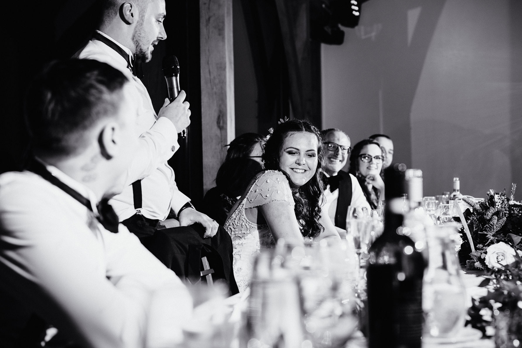 a bride smiles during wedding speeches