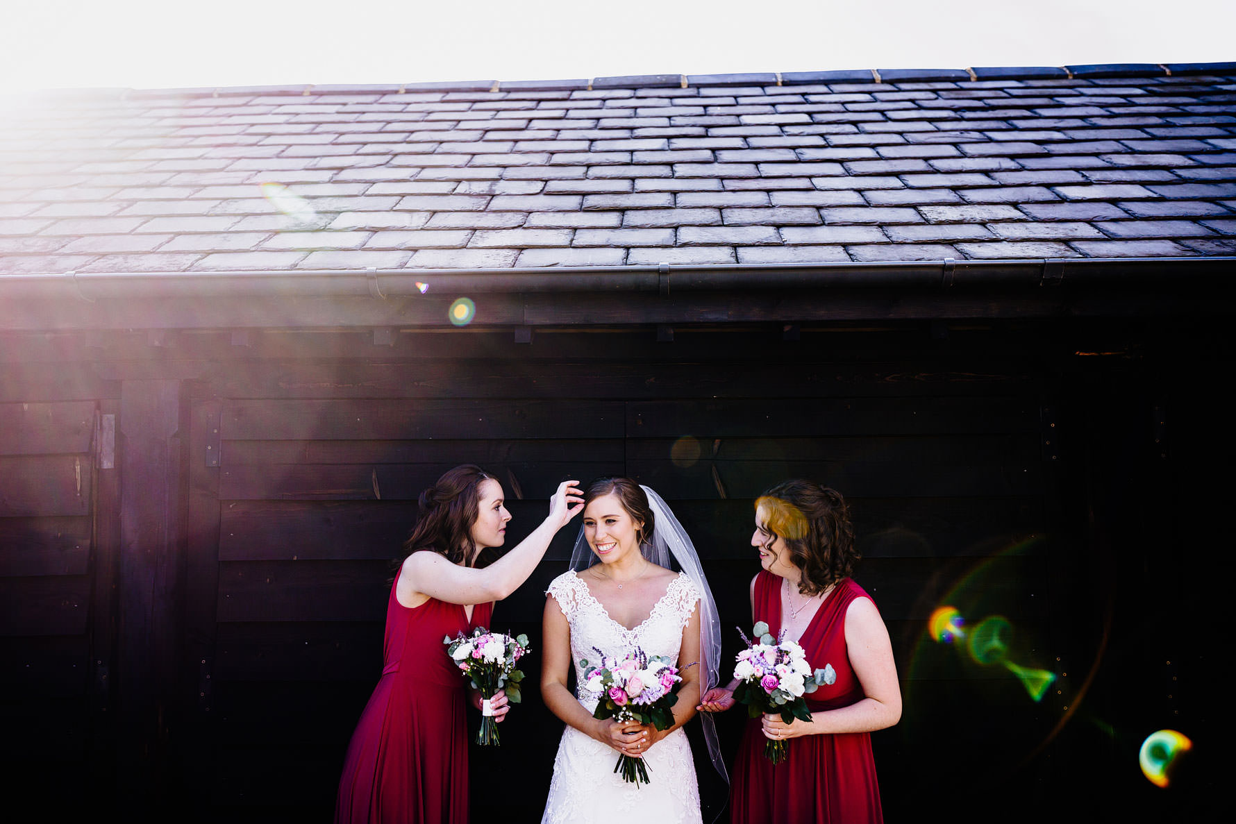bridesmaids prepare a bride for a photograph