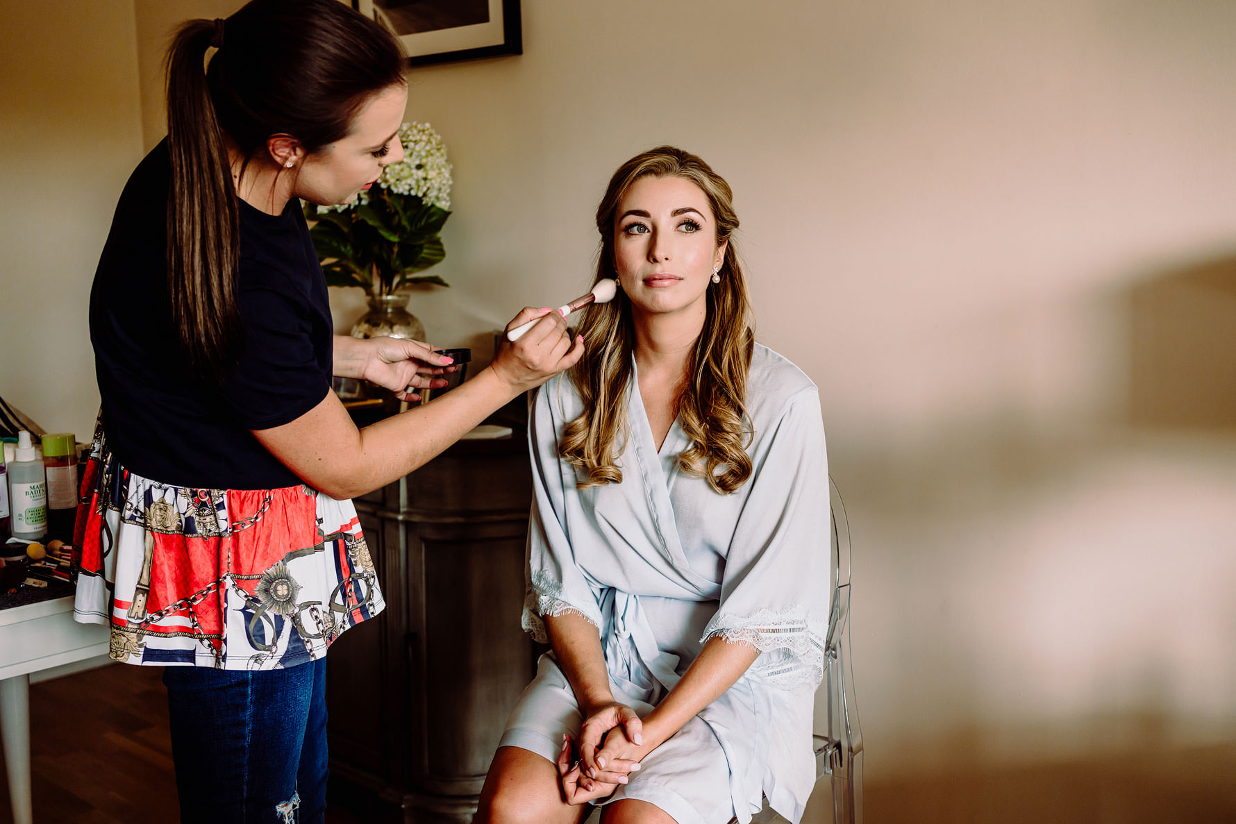 a bride has make up applied by her mua