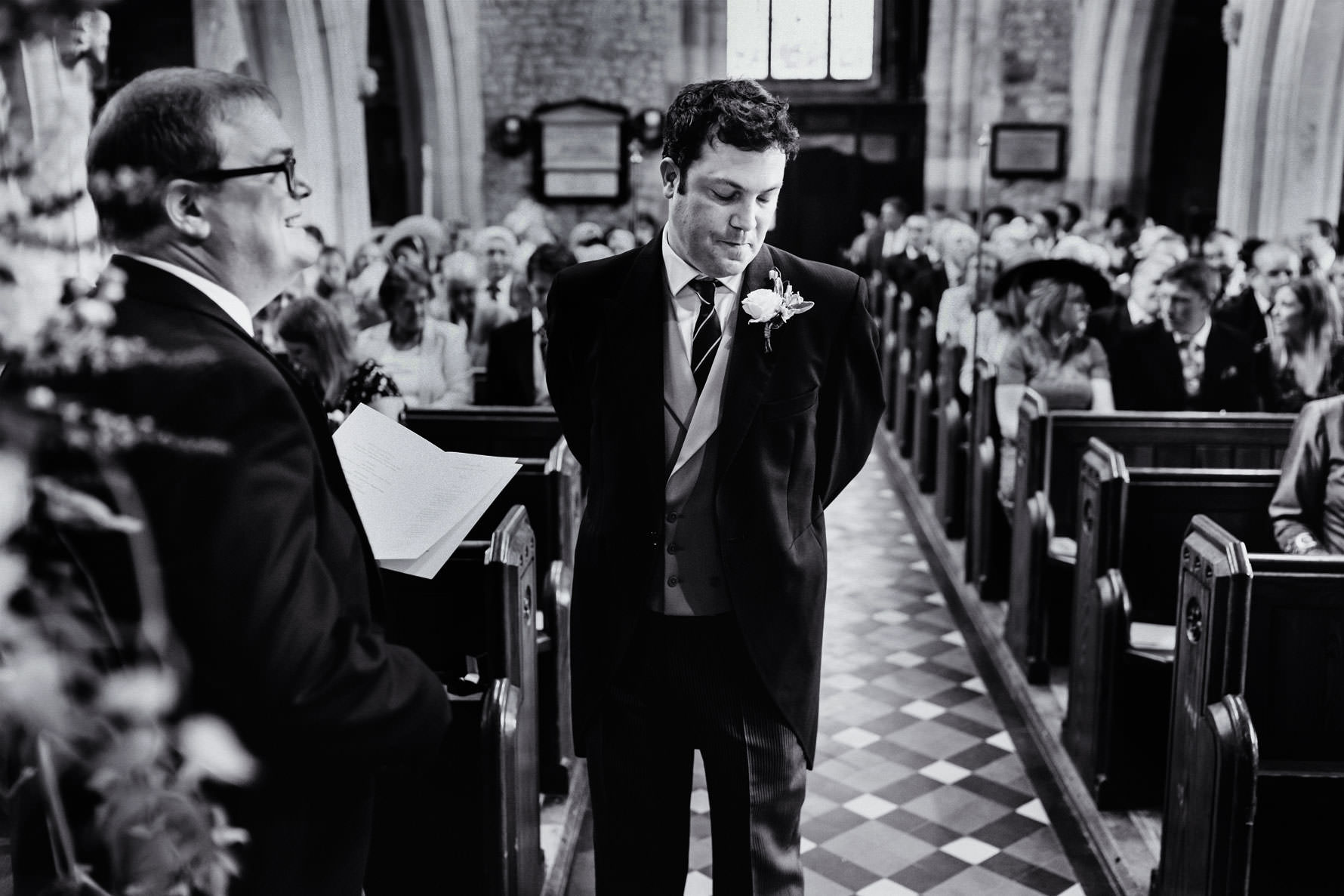 a groom stands nervously waiting for the bride