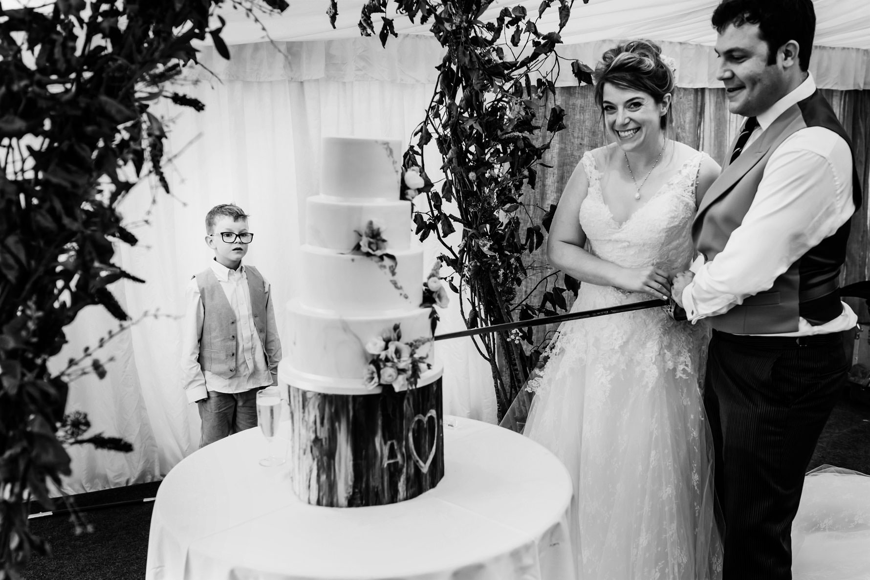a little boy stares at the wedding cake